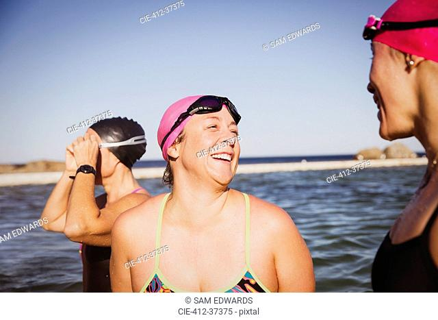 Laughing female open water swimmers talking at sunny ocean