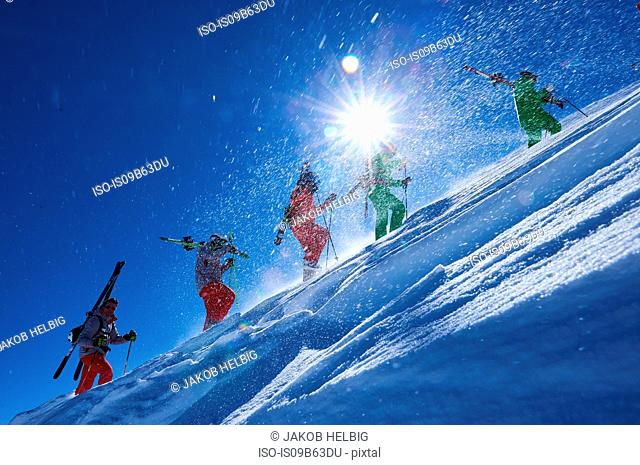 Five male skiers trudging up steep sunlit mountainside, Aspen, Colorado, USA
