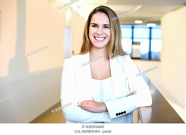 Portrait of young happy businesswoman in office corridor