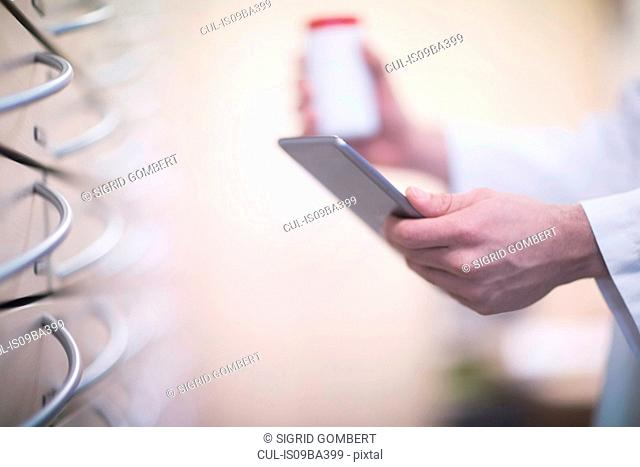 Male pharmacist holding pill bottle and digital tablet in pharmacy, close up of hand