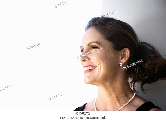 Portrait of mid-adult Caucasian female smiling and looking to side