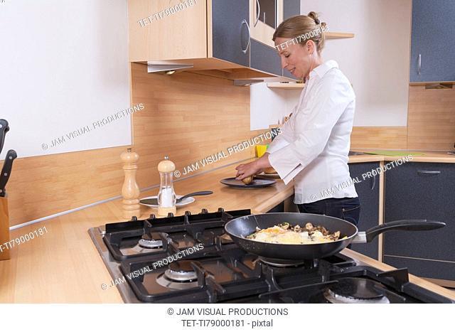 Woman preparing scrambled eggs for breakfast