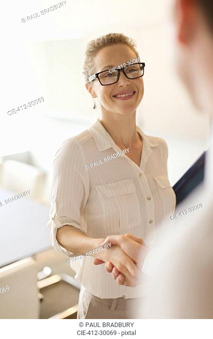 Smiling businesswoman shaking hands with businessman