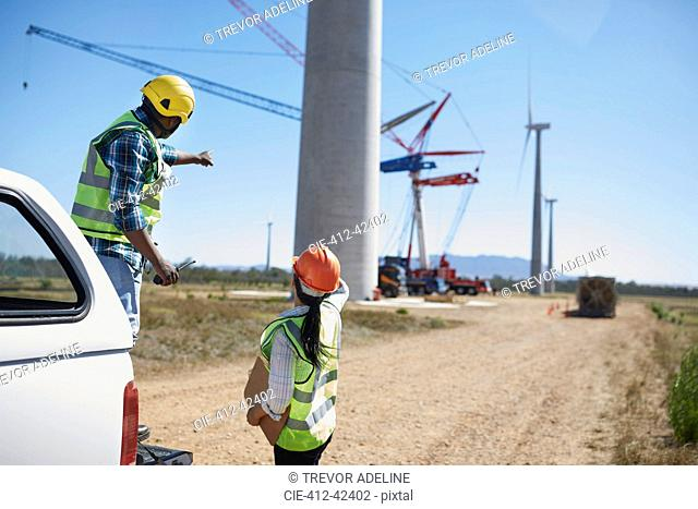 Engineers on dirt road at wind turbine power plant