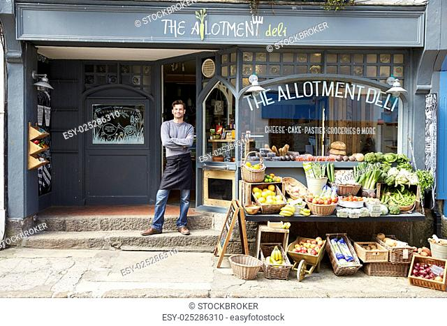 Male Owner Standing Next To Produce Display At Deli
