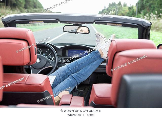 Young woman sitting stretching her legs in a car