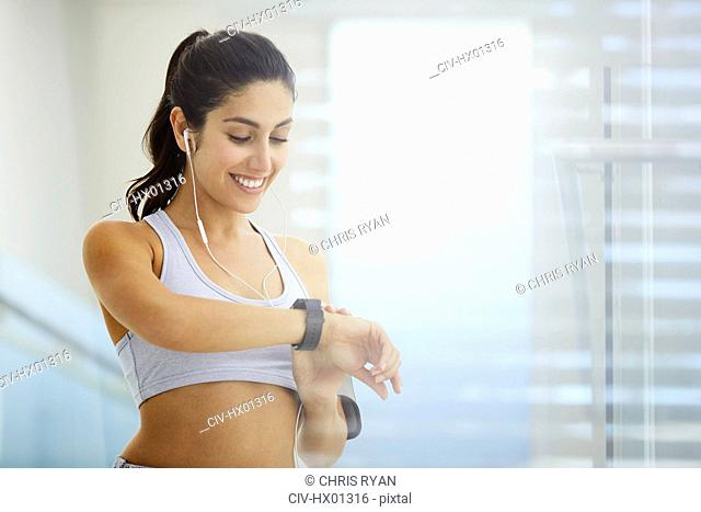 Woman exercising with headphones checking smart watch