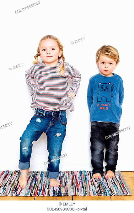 Portrait of young girl and boy against white background