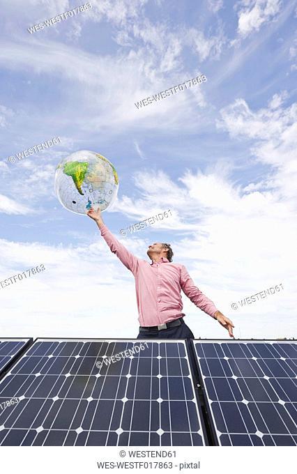 Germany, Munich, Mature man balancing globe on finger in solar plant