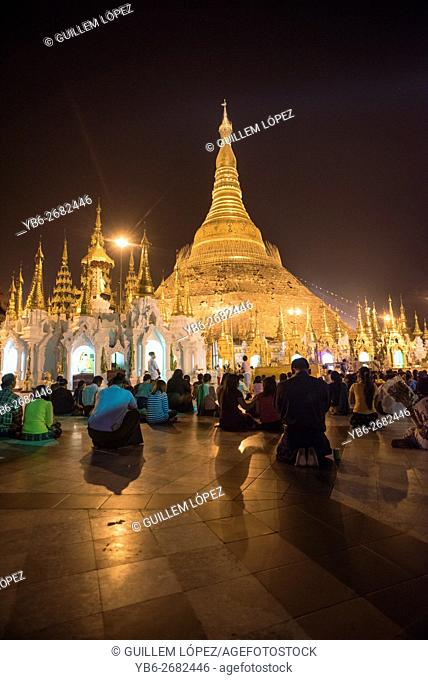 A group of people prying at the Shwedagon pagoda in Yangon, Myanmar