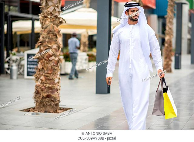 Man wearing traditional middle eastern clothing walking along street carrying shopping bags, Dubai, United Arab Emirates