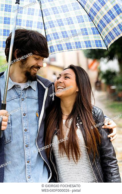 Happy young couple with umbrella