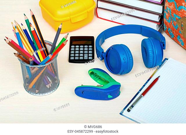 School supplies. School backpack, books, yellow sandwich box, metal stand for pencils with color pencils, stapler, headphones