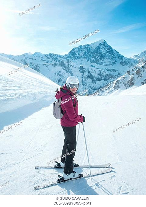 Young woman skier wearing helmet and ski goggles looking back in snow covered landscape, portrait, Alpe Ciamporino, Piemonte, Italy