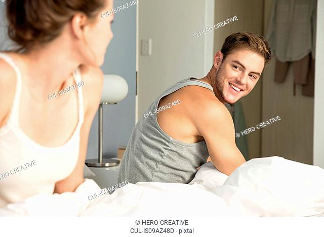 Happy young couple getting up from bed