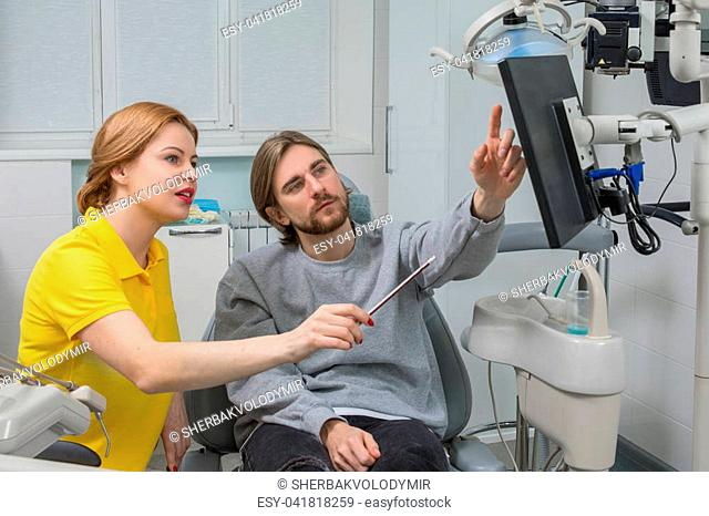 Femail Dentist shows a patient x-ray. Dental care Concept. Dental inspection is being given to Beautiful man surrounded by dentist