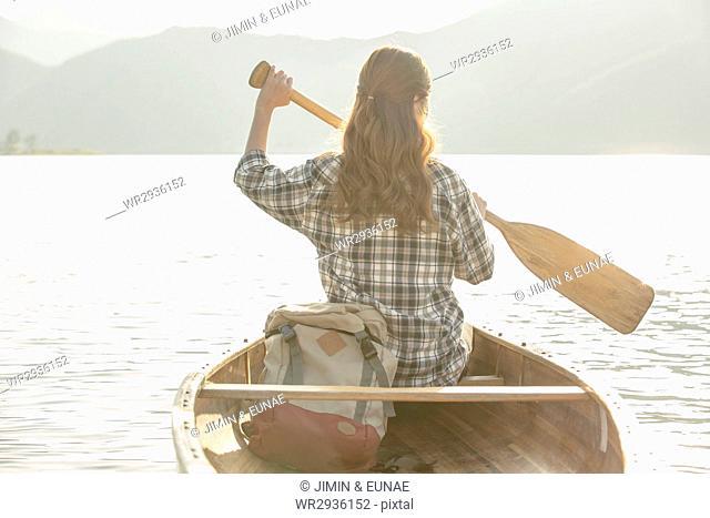 Back of young female traveler paddling a canoe