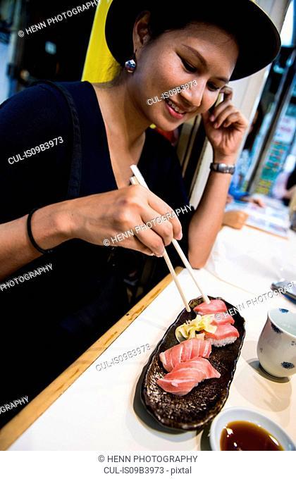 Woman eating sushi, Japan