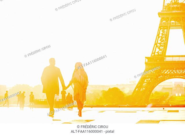 Couple holding hands near Eiffel Tower