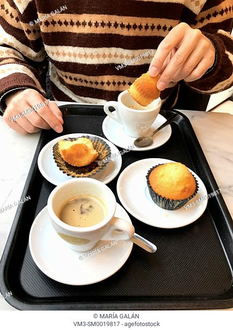 Man dipping a muffin in a cup of coffee, having breakfast