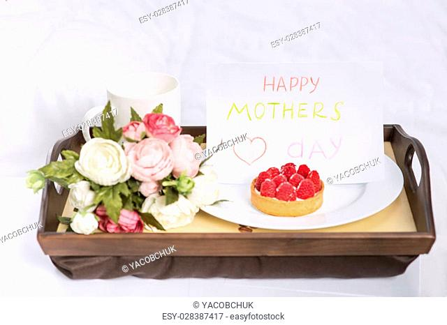 Perfect greeting. Festive breakfast containing fruit cake with coffee, flowers and card is on a wooden tray