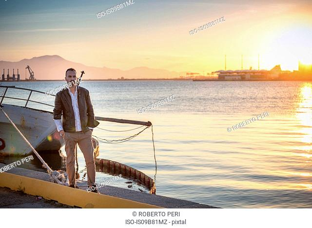Man standing by boat at sunset, looking at camera, Cagliari, Sardinia, Italy, Europe