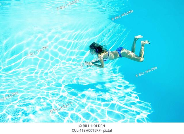 Woman in bikini swimming in pool
