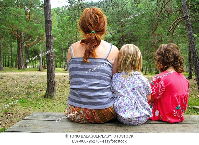 mother and daughters sitting back looking nature park forest wooden bench table