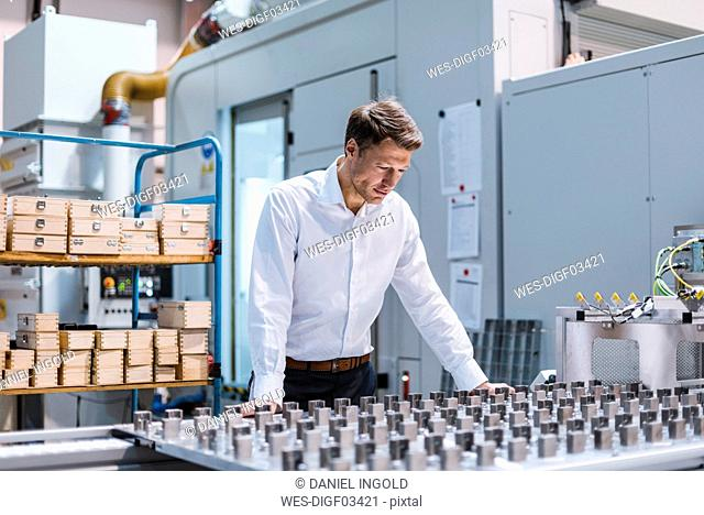 Businessman in factory looking at machine