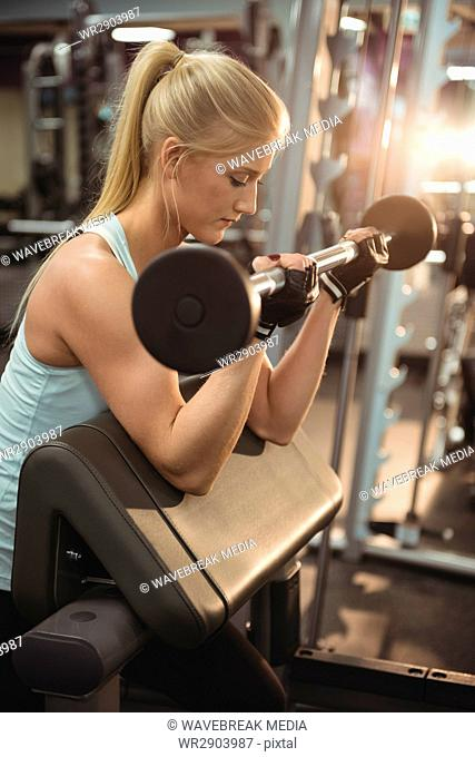 Fit woman exercising with barbell