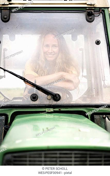 Portrait of smiling woman sitting in a tractor