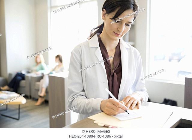 Dentist writing prescription at front desk