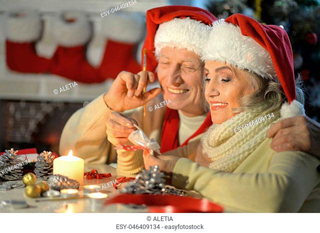 Portrait of happy senior couple in Santa hats preparing for Christmas or New Year