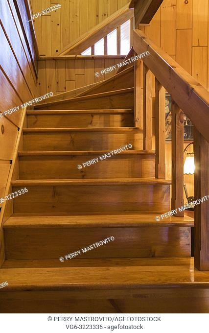 Pinewood staircase leading to the mezzanine inside a milled cottage style flat log profile home