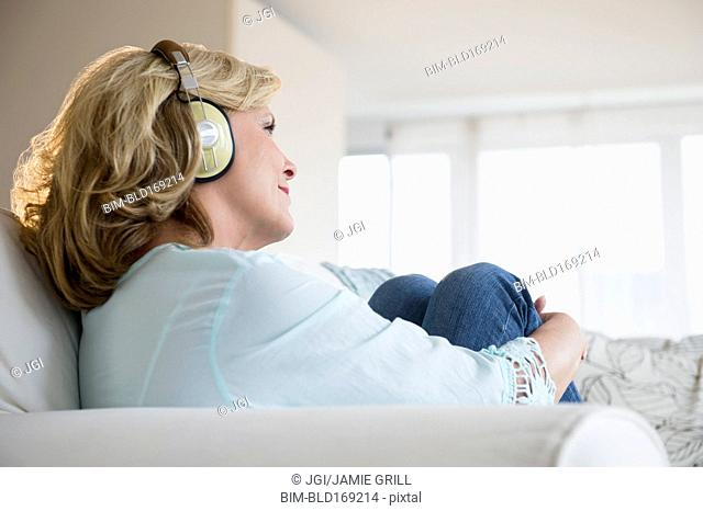 Caucasian woman listening to headphones on sofa