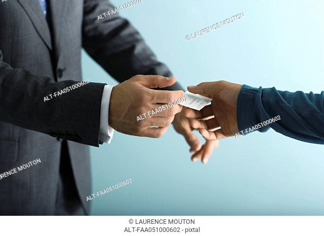 Businessman handing business card to client