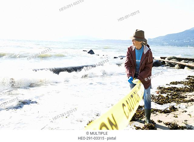 Beach cleanup volunteer rolling out caution tape on beach