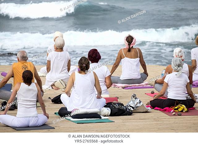 Yoga class overlooking Atlantic Ocean in Las Palmas, Gran Canaria, Canary Islands, Spain