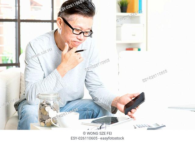 Mature 50s Asian man doing analysis on his business budget, looking on tablet pc and smart phone. Saving, retirement, retirees financial planning concept