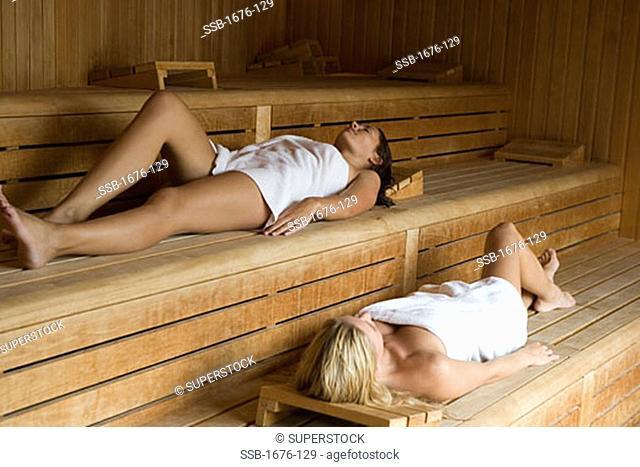 Two young women lying down in a sauna