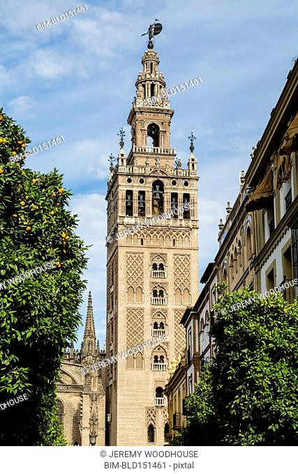 Low angle view of bell tower over Seville cityscape, Andalusia, Spain