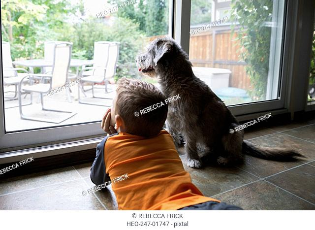 Curious boy laying at patio window with dog