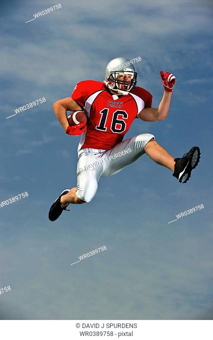 American Football player ball under arm going for it