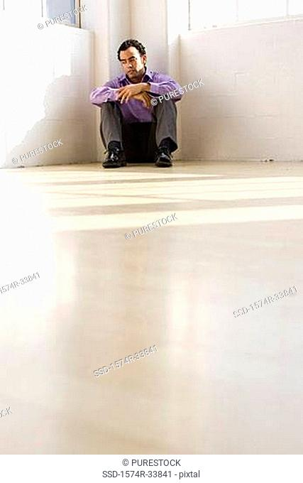 Businessman sitting on the floor in the corner of an office