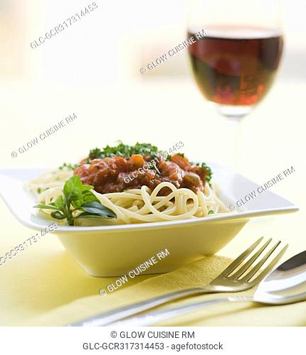 Close-up of spaghetti and meat with red wine