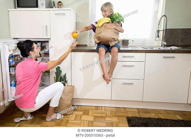 Boy giving an orange to his mother at refrigerator, Bavaria, Germany