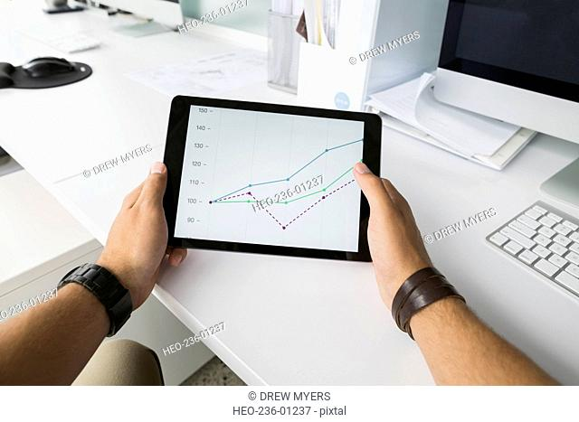 Businessman holding digital tablet with line graph
