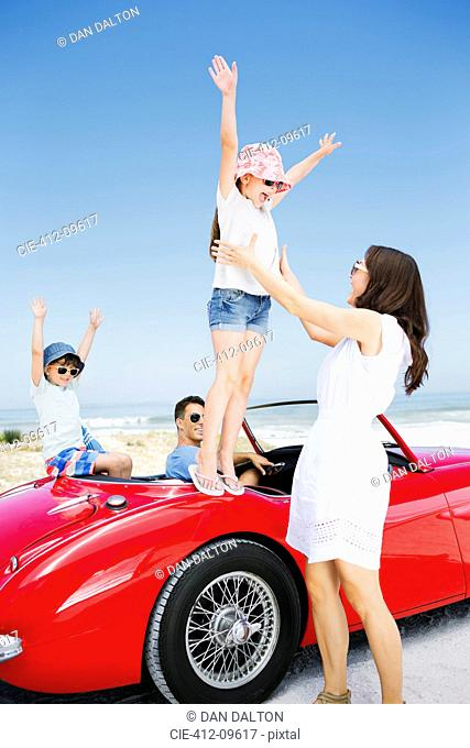 Girl jumping into mother's arms from convertible at beach