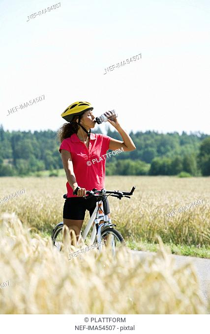 A woman riding a bike and drinking water in the countryside, Sweden