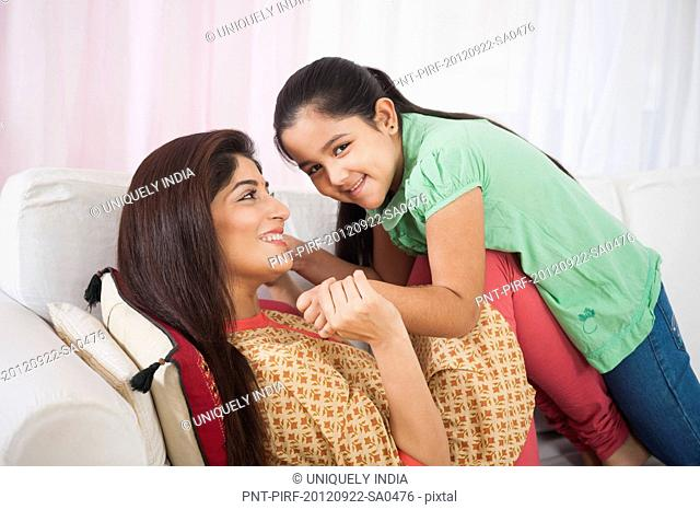 Woman playing with her daughter on a couch